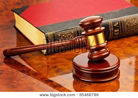 the gavel of a judge in court. lies on a desk.