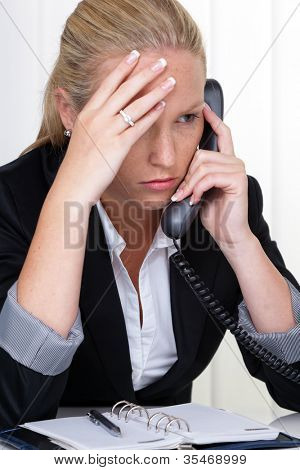 a frustrated woman telephoned the office. stress and strain in the workplace.
