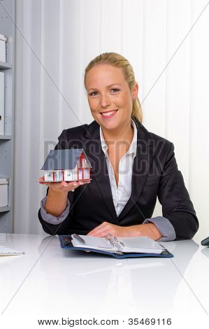 a young real estate agent with a model home in her office.