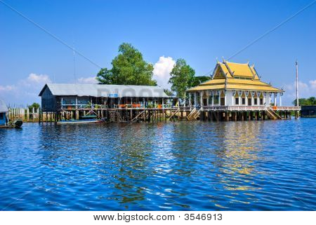 Floating House and temple on the Tonle sap lake with a small houseboat. Cambodia. poster