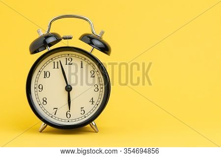 Alarm Clock At Almost 6 O'clock In The Morning On Yellow Background With Copy Space Using As Busines