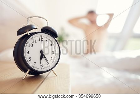 Alarm clock morning wake-up time on bedside table with man stretching on bed in background and copy space