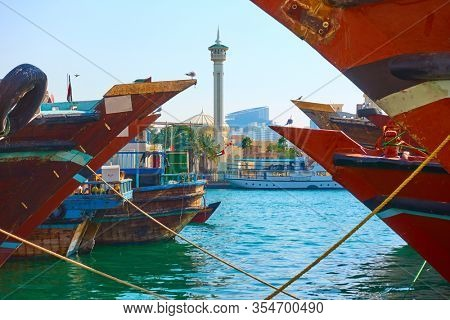 Heads of arabian ships dhow in Deira and minaret of Garand Mosque on the other side of the Creek in Dubai, United Arab Emirates (UAE)