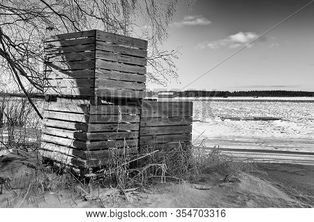 The Farmer Has Piled Three Wooden Crates By A Snowy Field At The Rural Finland. The Crates Have Been