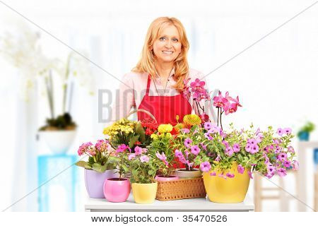 Female horticulturist standing with flower pots