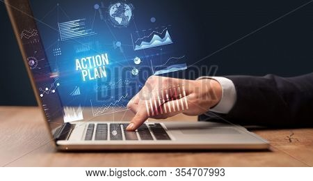 Businessman working on laptop with ACTION PLAN inscription, new business concept