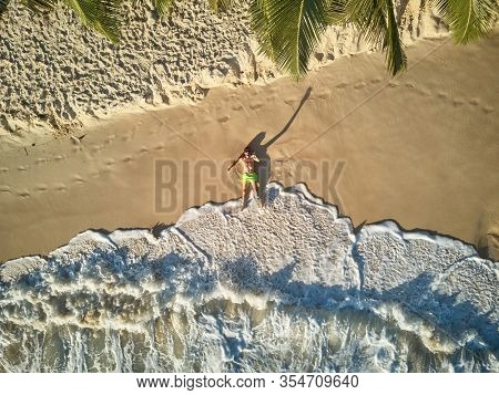 Man lying down on beach aerial top view drone shot at Seychelles, Mahe