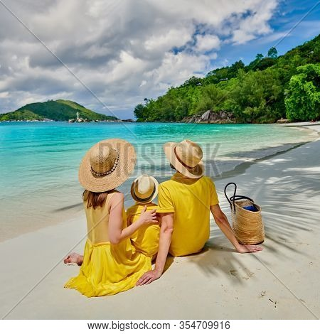 Family on beach, young couple in yellow with three year old boy. Summer vacation at Seychelles. Port Launay, Mahe.