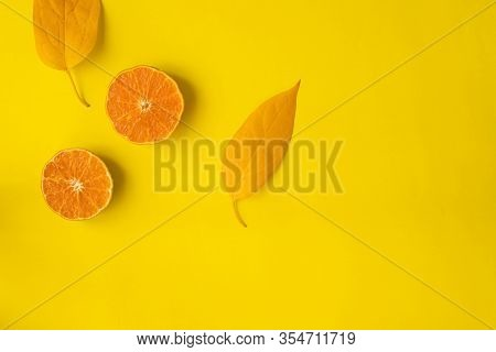 Sliced Orange Fruit And Yellow Fruit On Yellow Background With Copy Space.
