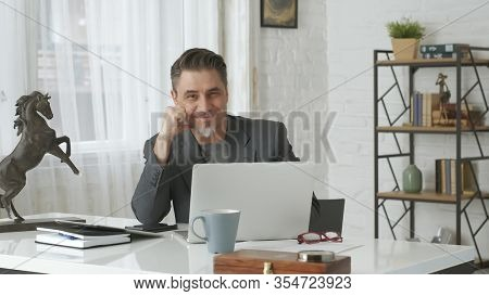 Older man working with laptop computer at home office, thinking, looking busy.
