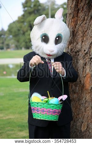 Easter Bunny. Business man wearing a Giant White Rabbit Head stands with an Easter Basket against a Tree. The Easter Bunny is loved world wide and is fun for all ages. Hop on down to the Easter Party.