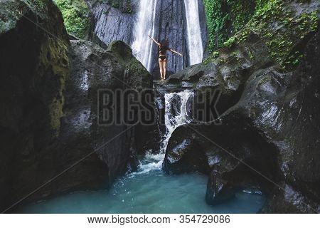 Woman Enjoying Near Hidden In Jungle Cascade Waterfall In Bali. Slim Body And Black Swimsuit, Fashio