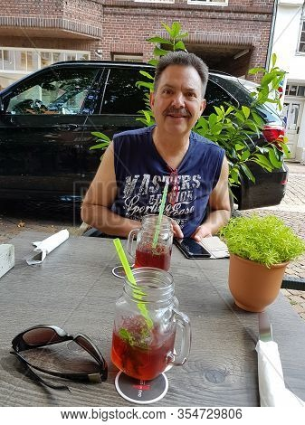 LÜneburg, Niedersachsen, Germany - Juli 27, 2018: Man Is Sitting In The Beer Garden Of A Restaurant