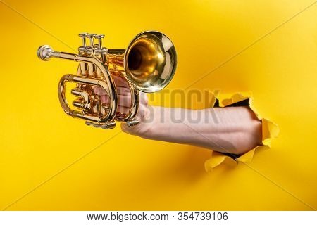 Hand Showing A Pocket Trumpet Through Torn Yellow Paper Background