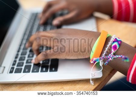 Close Up Of Teenage Girl Wearing Wristbands Typing On Laptop Computer Keyboard