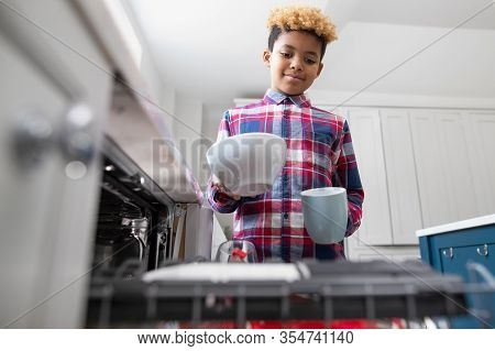 Boy Helping With Chores At Home By Stacking Crockery In Dishwasher