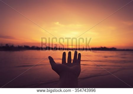 Man Open Hand Up On Tropical Sunset Background. Vintage Tone Color Style.