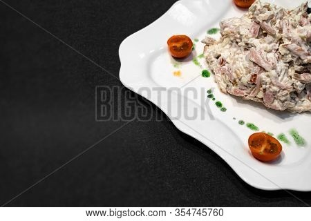 A Fragment Of A White Plate With Salad, Tomatoes And Green Sauce On A Black Background. Freespace.