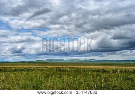 Traditional Steppe Landscape Of Central Asia. Steppe, Not High Mountains, Beautiful Clouds