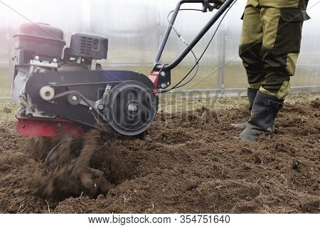 A Male Farmer Cultivates The Land In The Garden With A Cultivator In Clear Spring Weather Opposite T