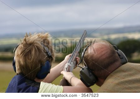 Young boy is taught how to shoot at the clay pigeons ** Note: Slight blurriness, best at smaller sizes poster