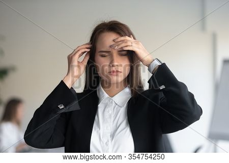 Stressed Millennial Female Office Worker Suffering From Sudden Head Pain.