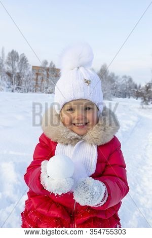 Little Beautiful Girl In A Red Coat And White Scarf Holds A Round Snowball In Her Hands And Smiles.