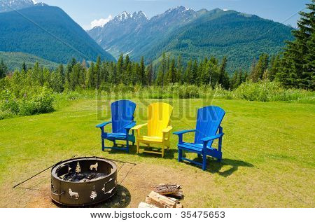 outdoor fireplace with three colorful chairs over fantastic mountain view