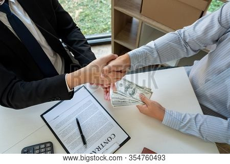 Businessman Giving Bribe Money Dollar Banknotes In Hands To Partner In A Corruption Scam, Dishonest