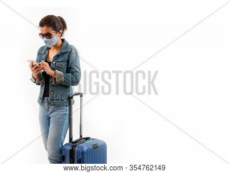 A Tourist In Medical Mask Stand Near Luggage And Using Phone Isolate On White Background . Novel Cov