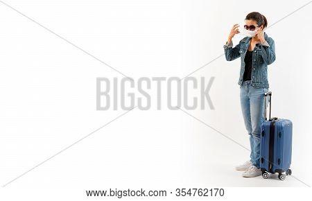 A Tourist In Medical Mask Stand Near Luggage Isolate On White Background . Novel Covid-19 Coronaviru