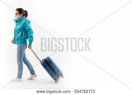 Tourist In Medical Mask Walking, Dragging Luggage Isolated On White Background . Novel Covid-19 Coro