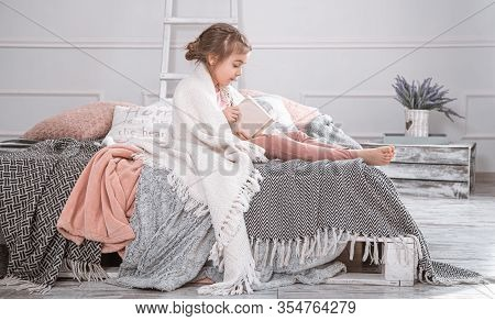 Cute Little Girl Reading A Book On The Bed.