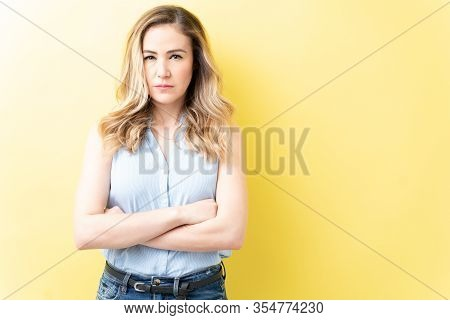 Angry Caucasian Woman In Casual With Arms Crossed Standing Against Yellow Background