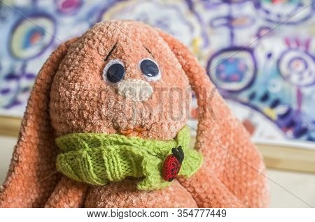 Knitted Bunny Toy Apricot Color On A Picturesque Background. Easter Photo.