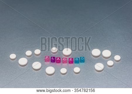 Placebo Pill. White Pills And Word Placebo On Silver Grey Background. Placebo Effect, Fake Medical T