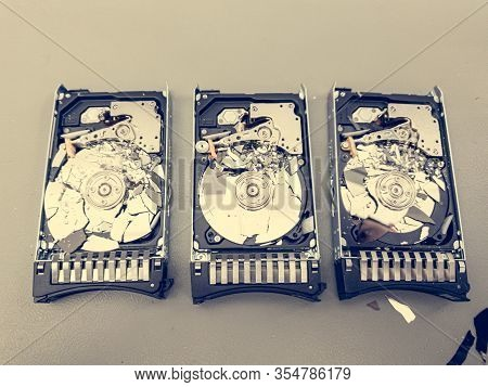 Three Hard Disk Drives With Shattered Platter On A Table.