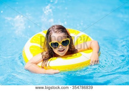 Child In Swimming Pool On Inflatable Yellow Lemon Ring. Little Girl Learning To Swim With Orange Flo