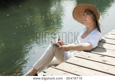 Woman relaxing while reading a book by river