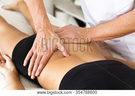 Massages And Physiotherapy To A Woman On Her Back