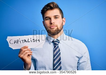 Young blond businessman with beard and blue eyes holding paper with capitalism message with a confident expression on smart face thinking serious
