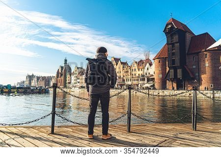 Male Tourist With A Backpack In Sunny Winter Weather Walks Sightseeing In The Old Town Of Gdansk In
