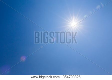 Shining Sun On Clear Blue Sky. Lens Flare Of Sunlight On Blue Sky Background. Bright Sun On Blue Sky