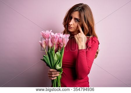 Young beautiful brunette woman holding bouquet of pink tulips over isolated background Pointing to the eye watching you gesture, suspicious expression