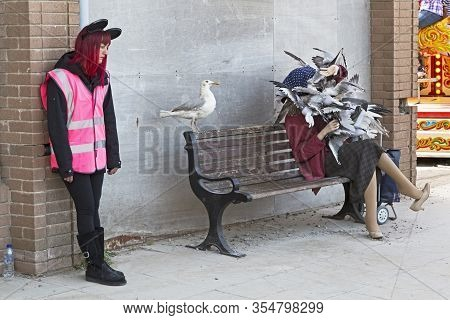 Weston-super-mare, Uk - September 10, 2015: An Attendant Standing Next To A Sculpture Of A Woman Bei