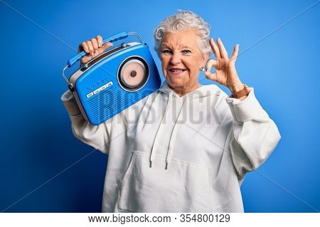 Senior beautiful woman holding vintage radio standing over isolated blue background doing ok sign with fingers, excellent symbol