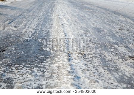 Dangerous Driving Conditions. Icy Road With Tracks From The Wheels Of Cars . The Concept Of Safe Dri
