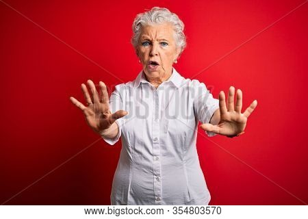 Senior beautiful woman wearing elegant shirt standing over isolated red background doing stop gesture with hands palms, angry and frustration expression
