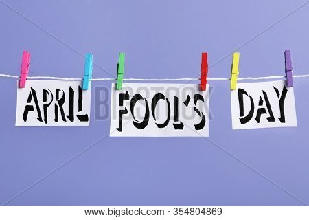Words April Fool's Day With Pegs On Laundry Line Against Violet Background