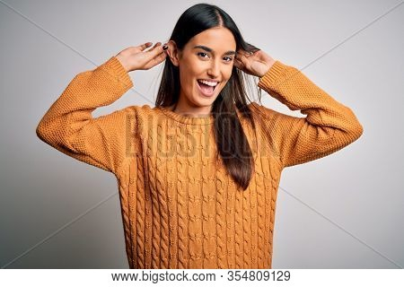 Young beautiful brunette woman wearing casual sweater over isolated white background Smiling pulling ears with fingers, funny gesture. Audition problem
